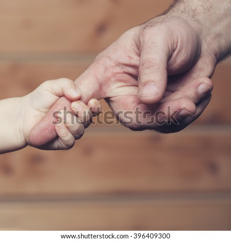 Closeup of two touching hands of small baby boy holding finger of male father as symbol of family love and trust on blurred wooden background, square picture - stock photo