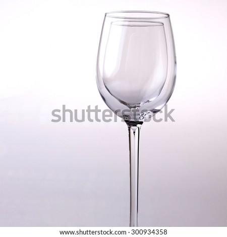 Closeup of two transparent clear crystal empty wine glasses standing close to each other in row isolated on chromium white and grey background copyspace, square picture - stock photo