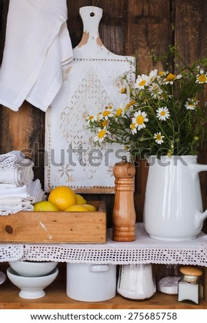 Closeup of two white wood rustic kitchen shelves with assorted household items. Various objects, include, pepper shaker, cups, pitchers bottles, lemons and bouquet of chamomile flowers. - stock photo
