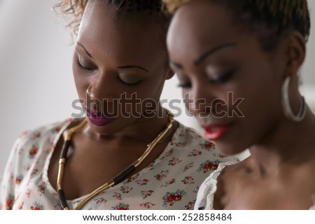 Closeup of two young african cheerful women friends together - stock photo