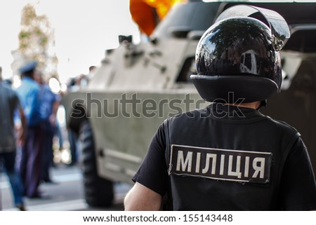 closeup of ukrainian riot policeman wearing protective vest and helmet with armored military vehicle in background. - stock photo