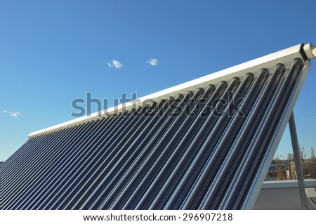 Closeup of vacuum solar water heating system on the house roof against blue sky. Energy saving concept. - stock photo