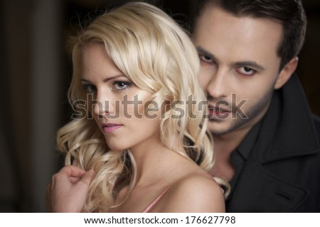 closeup of vampire kissing woman - stock photo