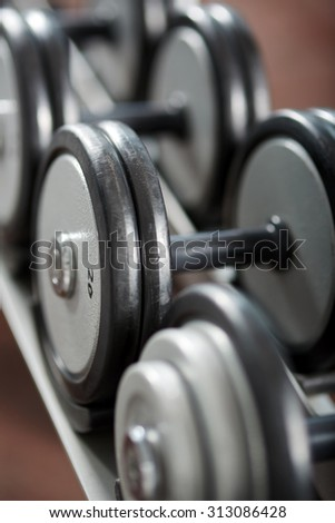 Closeup of various dumbbells on the rack in the gym