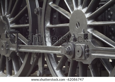 Closeup of vintage steam engine's black, iron wheel - stock photo