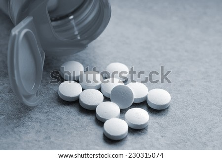 Closeup of vitamin pills and bottle. Image toned blue for effect. - stock photo