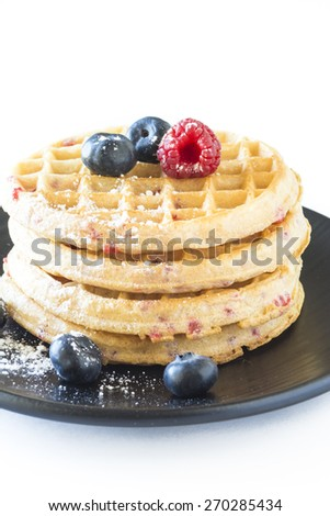 Closeup of waffle stack and berries on a black plate.