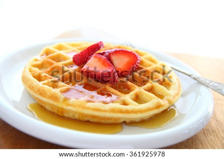 Closeup of waffle with fresh strawberries and syrup with copy space - stock photo