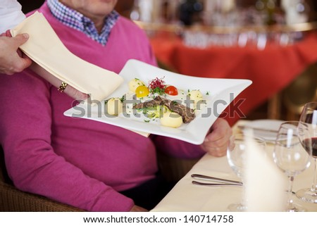 Closeup of waiter's hand serving food to male customer at restaurant table - stock photo