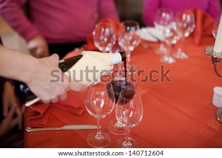 Closeup of waitress hand's pouring red wine in glass for customers at restaurant - stock photo