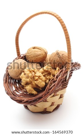 Closeup of walnut without shell and stack of walnuts in wicker basket. Isolated on white background - stock photo