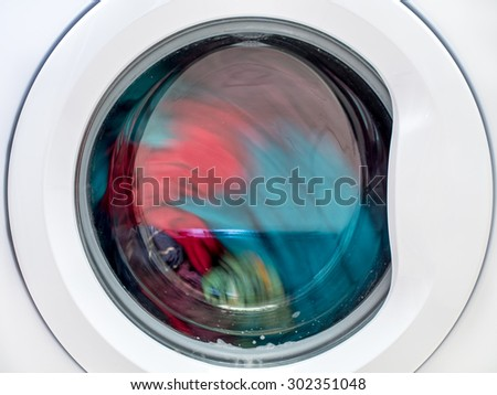 Closeup of washing machine door with spinning laundry - stock photo