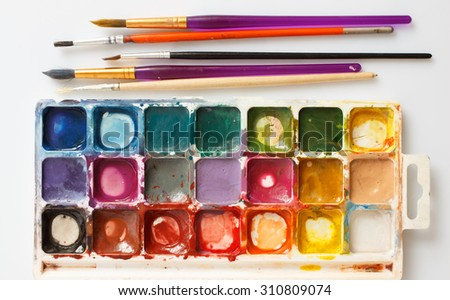 Closeup of water-color paint-box and paint brushes - stock photo
