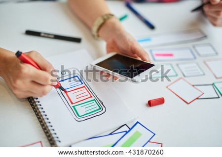 Closeup of web designers prototyping responsive website for mobile devices - stock photo
