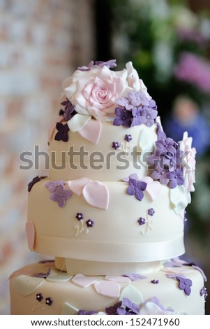 Closeup of wedding cake detail showing ornate pink and purple flower decoration