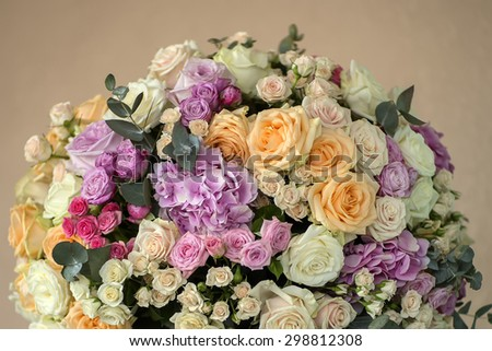 Closeup of wedding posy of fresh beautiful flowers of roses and peony white pink violet purple yellow lilac and orange colours  on beige background, vertical picture - stock photo