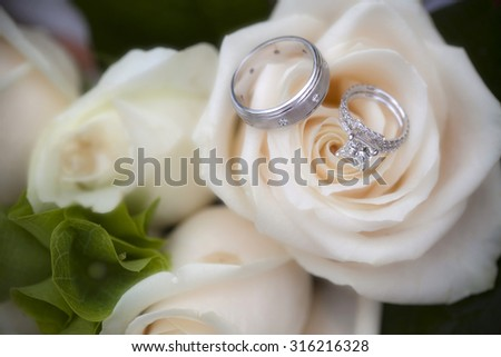 Closeup of wedding rings on a rose bouquet - stock photo