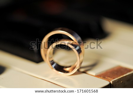 closeup of wedding rings on piano - stock photo