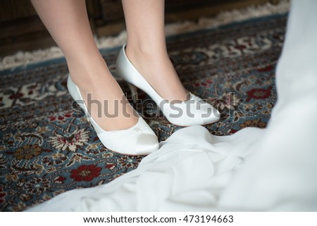 Closeup of wedding shoes: bride getting ready for the wedding
