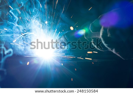 Closeup of welding metal with arc, sparks and torch - stock photo