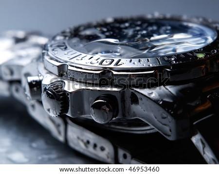 Closeup of wet metal wrist watch. - stock photo