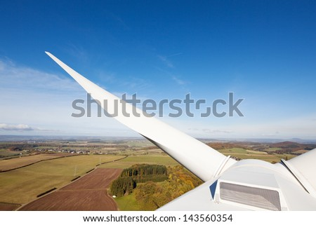 Closeup of white blade of windmill in farm against blue sky - stock photo