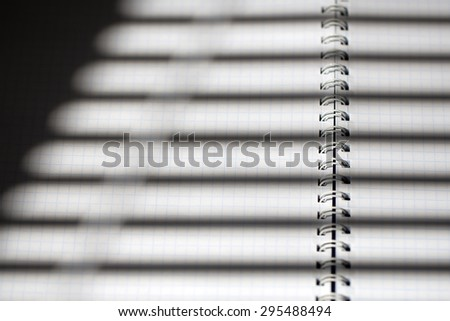 Closeup of white cage blank open note pad with spiral and jalousie shade of stripes copyspace, horizontal picture - stock photo