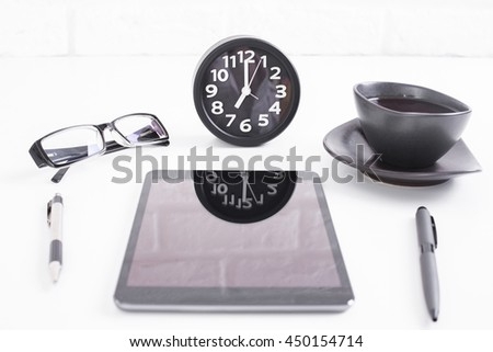 Closeup of white desktop with clock reflected on blank tablet screen, pens, glasses and coffee cup on white birck wall background. Mock up - stock photo
