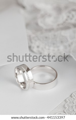Closeup of white golden wedding rings on gray background. Bride ring with diamonds. Shallow focus