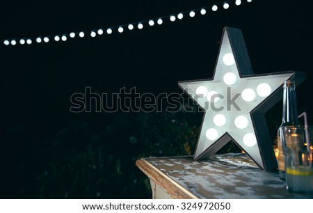 Closeup of white handmade star lamp with light bulbs over a wooden table with drinks and lights garland in the background in a outdoors party - stock photo