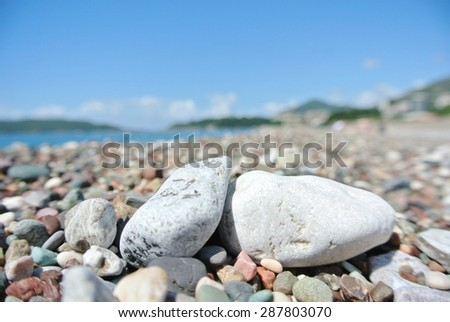 Closeup of white pebbles on the beach, on a sunny summer day.  - stock photo