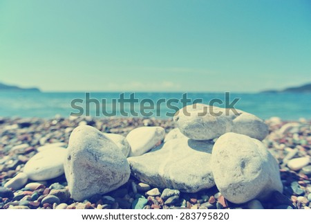 Closeup of white pebbles on the beach, on a sunny summer day. Image filtered in faded, washed out, retro style; summer vintage concept. - stock photo