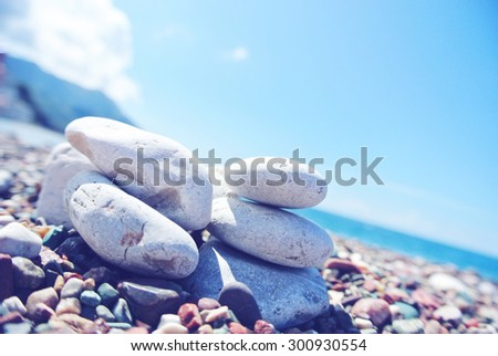 Closeup of white pebbles on the beach, on a sunny summer day. Image filtered in faded, washed out, retro style; summer vintage concept. Tilted perspective, personal pov. - stock photo