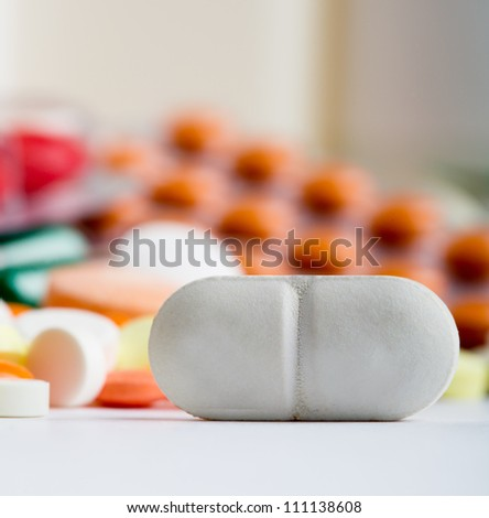 Closeup of white pill with various medicines on background - stock photo