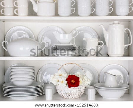 Closeup of white plates and dinnerware in a cupboard. A basket of white and red roses is centered on the bottom shelf. Items include, plates, coffee cups, saucers, soup tureen, tea pot, and gray boats - stock photo