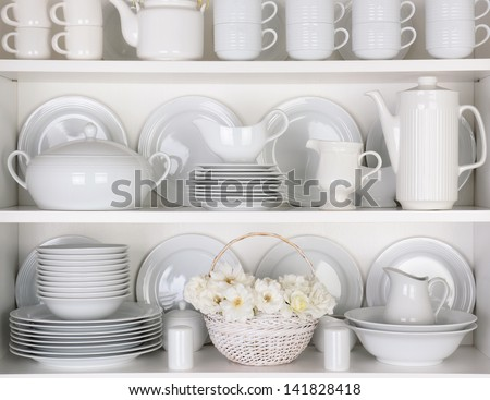 Closeup of white plates and dinnerware in a cupboard. A basket of white roses is centered on the bottom shelf. Items include, plates, coffee cups, saucers, soup tureen, tea pot, and gravy boats. - stock photo