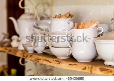 closeup of white plates and dinnerware in a cupboard, items include, plates, coffee cups, saucers, soup tureen, tea pot, and gravy boats