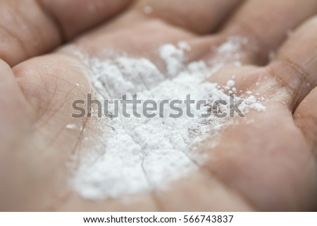 Closeup of white powder on hand