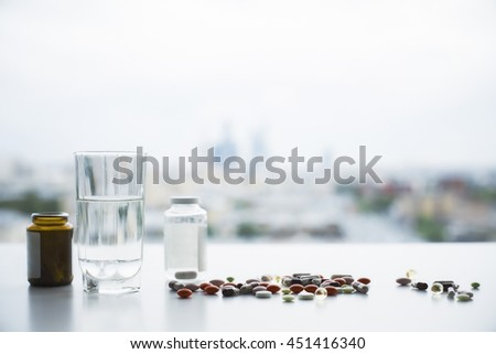 Closeup of white table with colorful pills, medicine bottles and glass of water on blurry city background - stock photo