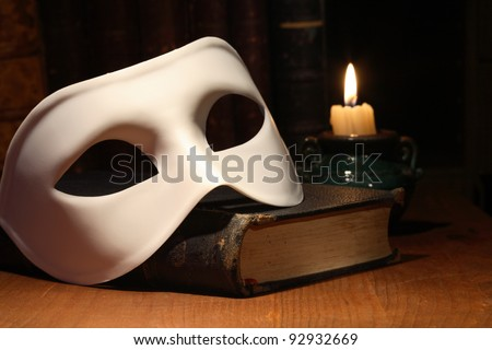 Closeup of white venetian mask lying on vintage old book near lighting candle