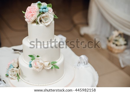Closeup of white wedding cake with roses