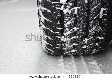 Closeup of winter tire on a road covered with snow - stock photo