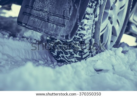 Closeup of winter tyre  on a  snowy road - stock photo