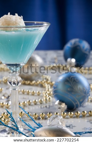 Closeup of Winter Wonderland Cocktail, garnished with coconut vanilla ice cream ball on Christmas decorated holiday table with Christmas ornaments. Holiday cocktails series.  - stock photo