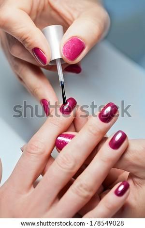 Closeup of Woman applying nail varnish to finger nails  - stock photo