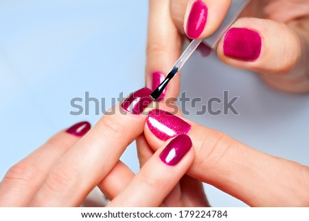 Closeup of Woman applying nail varnish to finger nails  - stock photo