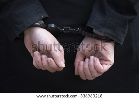 closeup of woman being handcuffed behind her back - stock photo