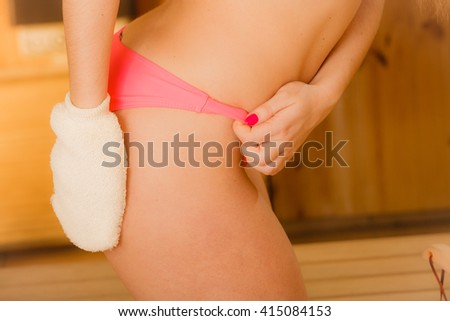 Closeup of woman body ass in wood finnish spa sauna massaging skin with exfoliating glove. Girl in bikini relaxing. Skincare concept.