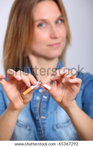 Closeup of woman breaking cigarette