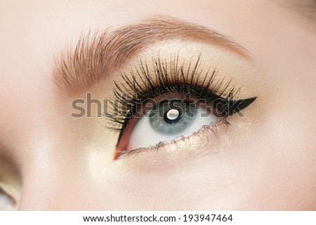 Closeup of woman eye with beautiful makeup with black eyeliner - stock photo